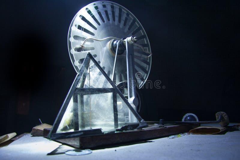 Старые электростатическая машина, генератор Wimshurst и пирамида стекла на черной предпосылке Концепция образования физики стоковая фотография rf