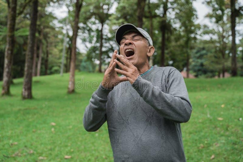 Старый азиатский человек чихая имеющ грипп стоковая фотография