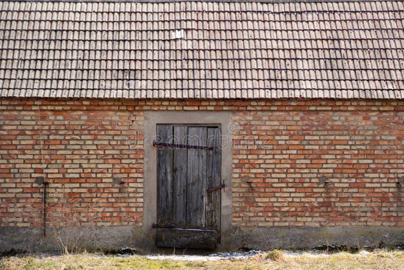 Старый амбар кирпича с деревянными дверями стоковые изображения rf