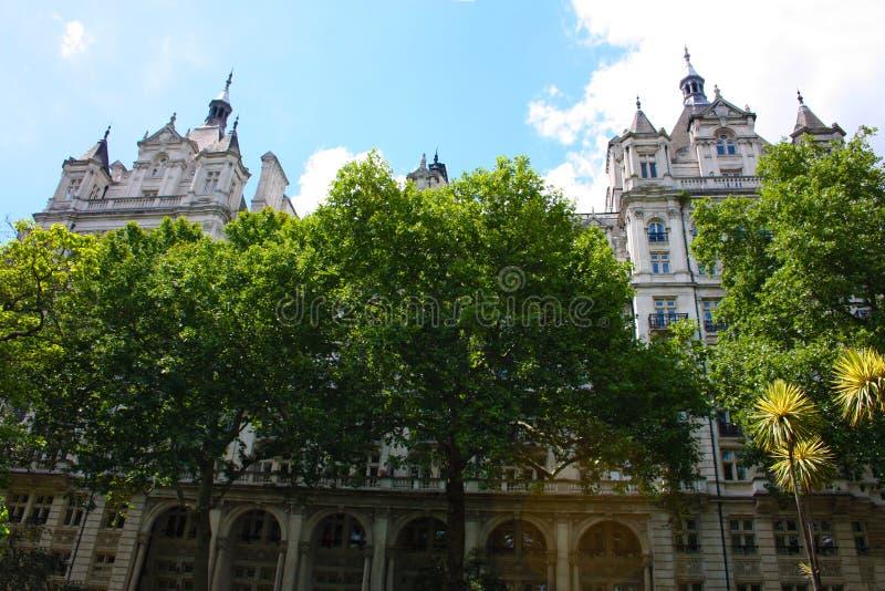 Старый английский дворец с парком на котором сочные зеленые деревья растут стоковые изображения rf