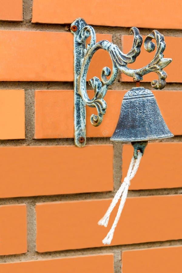 Старый бронзовый колокол с веревочкой на красной кирпичной стене богачи стоковые изображения rf