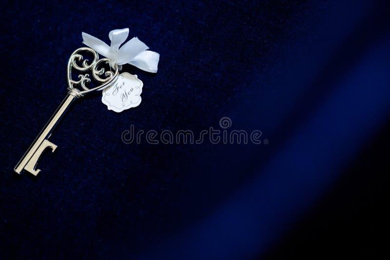 Старый винтажный ключ в предпосылке ткани сатинировки стоковые изображения