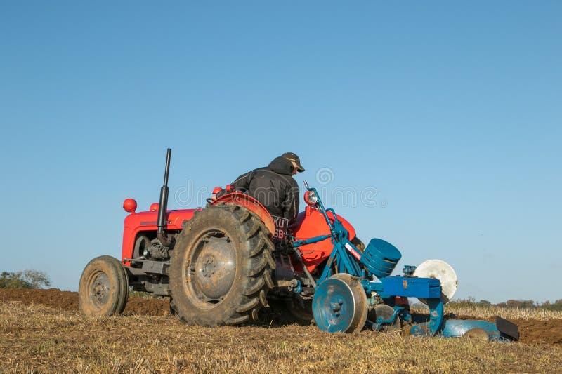 старый винтажный красный пахать тракторов стоковое изображение