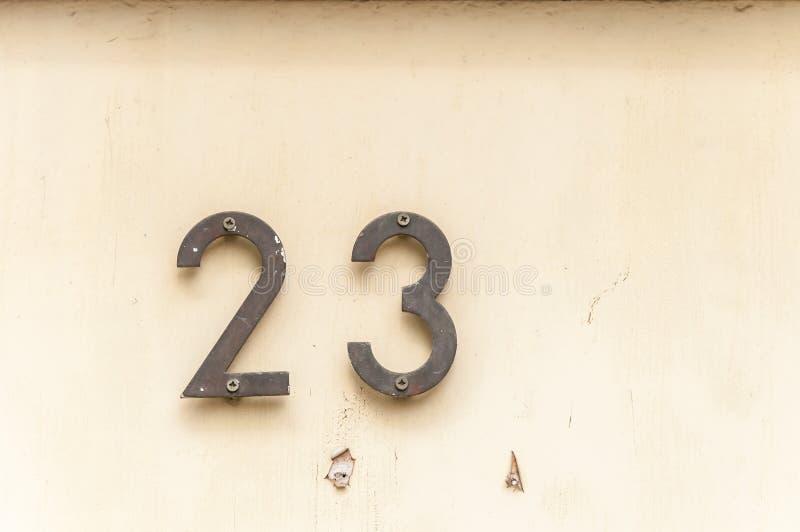 Старый винтажный металл 23 адреса дома на фасаде гипсолита покинутой стены дома внешней на стороне улицы стоковое изображение rf