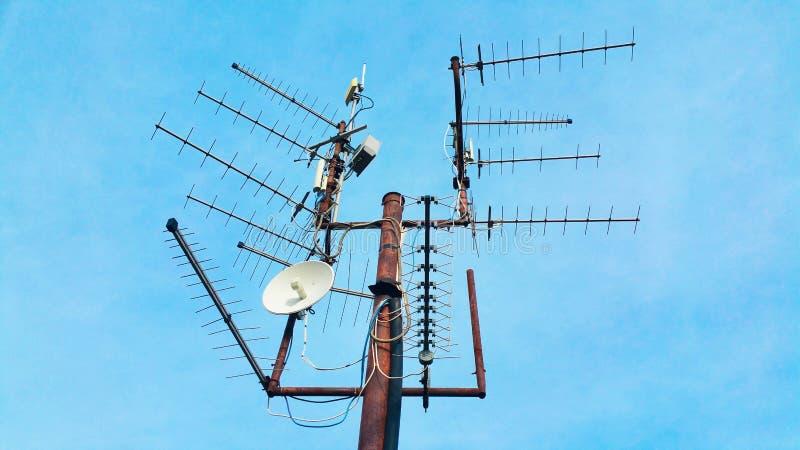 Старый винтажный ржавый рангоут телевидения с много антенн указывая н стоковое изображение rf