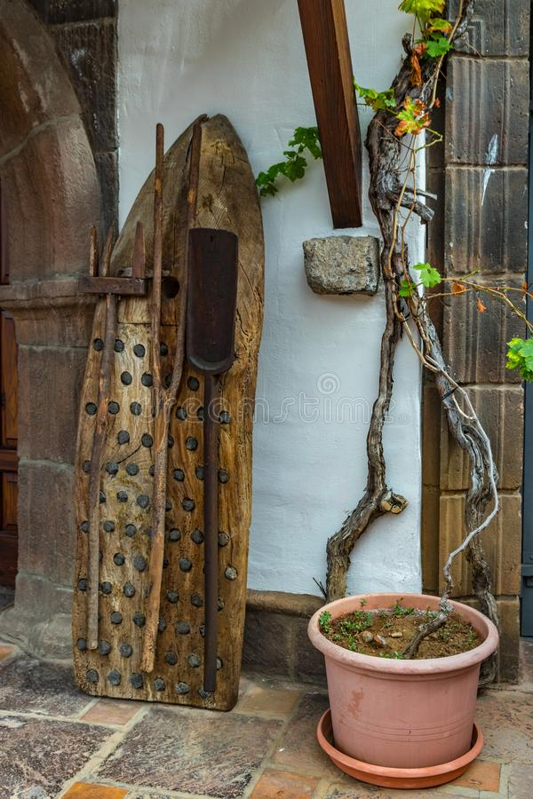 Старый винтажный традиционный молотильщик сделанный камня древесины и огнива с другими аграрными инструментами положился против с стоковые изображения rf