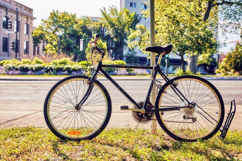 Старый винтажный черный велосипед припаркованный около дороги стоковая фотография