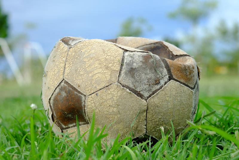 Старый выкачанный футбольный мяч, старый выкачанный футбол на зеленой траве стоковое изображение