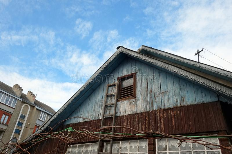 Старый деревянный дом с лестницей на предпосылке конкретного жилого дома стоковые изображения rf