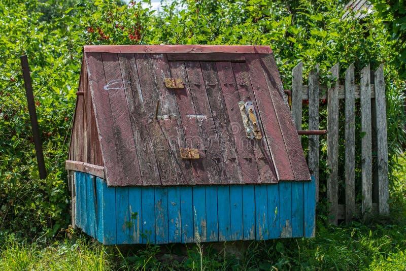 Старый деревянный колодец с домом в сельской местности Старый колодец деревни на фоне перерастанного сада стоковые изображения