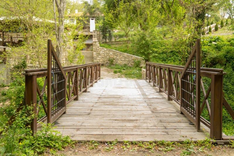 Старый деревянный мост в глубоком лесе водя к сельской местности стоковое изображение