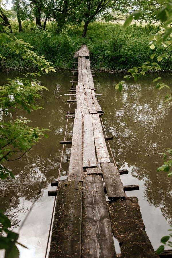 Старый деревянный мост, деревянный мост через небольшое реку, мост с природой стоковые изображения rf
