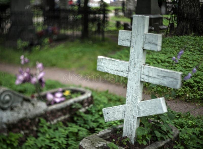 Старый деревянный правоверный серьезный крест в кладбище с расплывчатой предпосылкой с цветками и серьезными загородками стоковая фотография rf