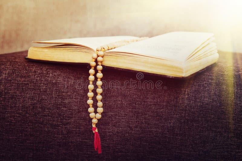 Старый деревянный розарий отбортовывает на книге церемоний стоковое изображение rf