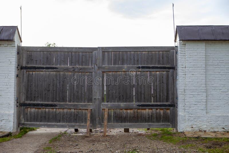 Старый деревянный строб с грязной улицей и 2 деревянных balks в серой загородке кирпича стоковое фото rf
