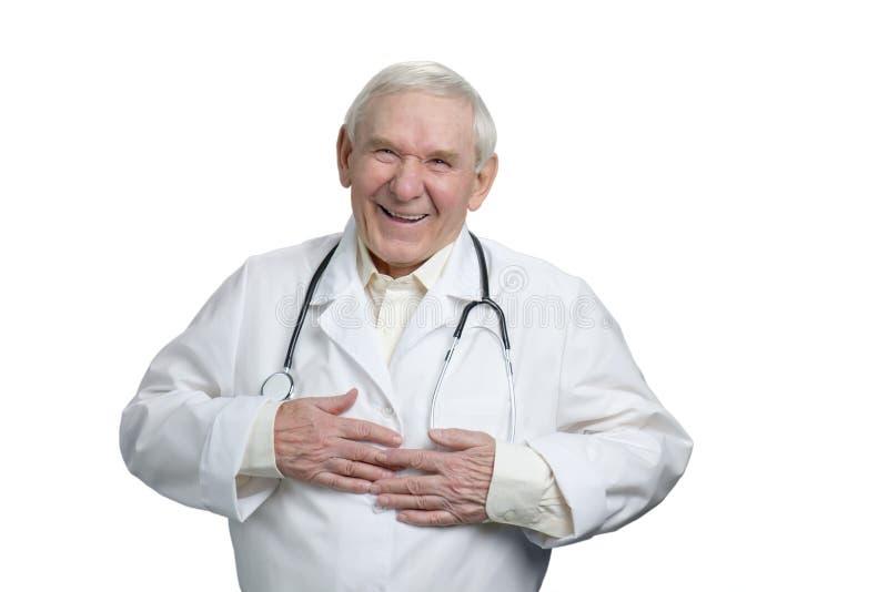 Старый доктор смеясь над heartily касающся животу стоковые фотографии rf