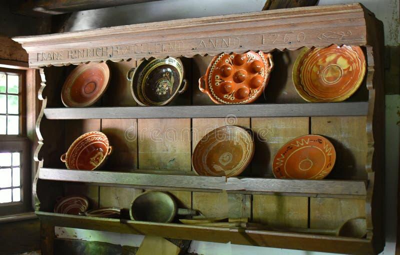 Старый дом в деревне фермера Блюда керамических и металла Омедняет и сковороды для центра В деревянном кухонном шкафе стоковая фотография