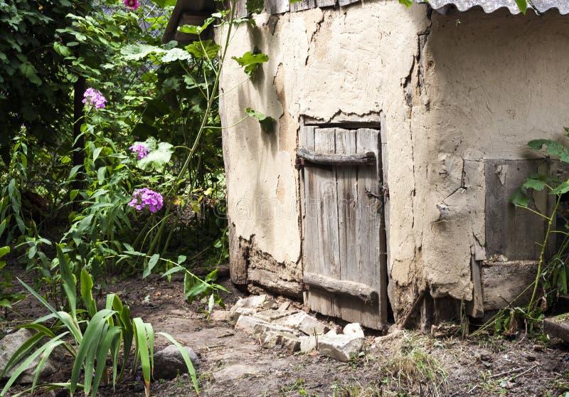 Старый дом козы удара с деревянной дверью в саде сельской местности стоковые изображения