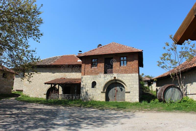 Старый дом сделанный камня с деревянной дверью и большим бочонком стоковая фотография rf