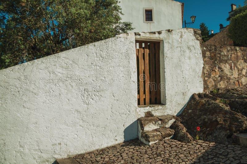 Старый дом с побеленной стеной и небольшая дверь в Marvao стоковая фотография