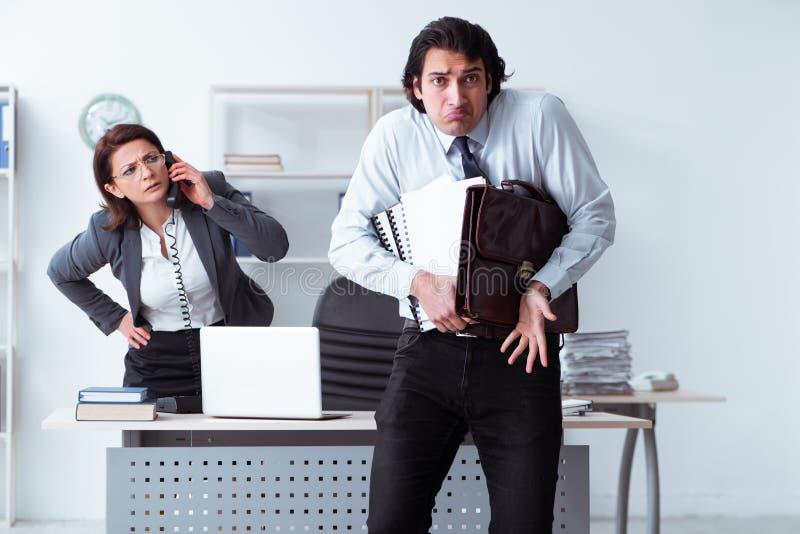 Старый женский босс и молодой мужской работник в офисе стоковая фотография