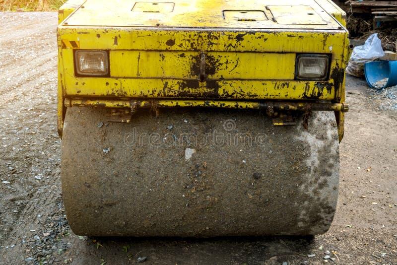 Старый желтый передний ролик дороги на дороге non-asphail стоковая фотография rf