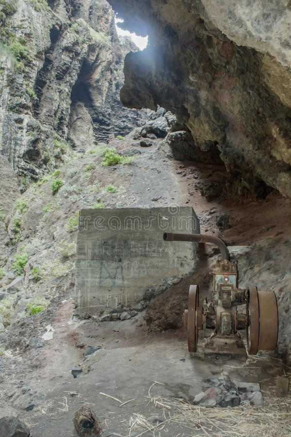 Старый заброшенный водяной насос в горной пещере Канарский остров, Тенерифе, каньон Маска долина с камнями, большими камнями, зел стоковое фото