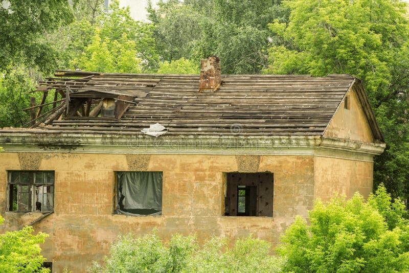 Старый загубленный дом среди зеленых деревьев стоковая фотография rf