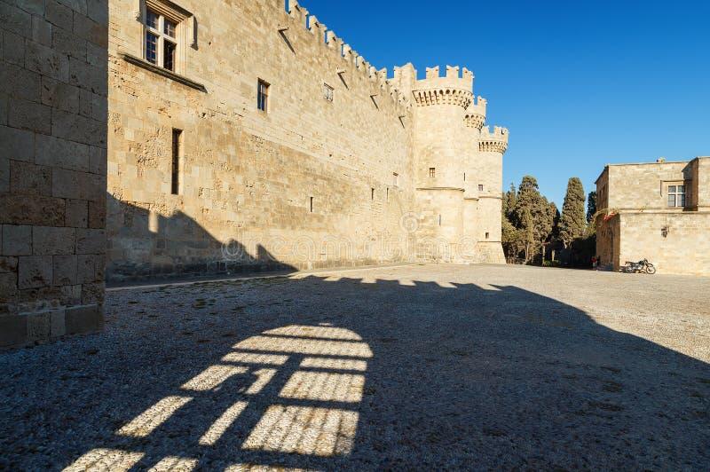 Старый замок Родоса с главной площадью посмотрите тень от загородки и персоны стоя в ей стоковое изображение rf