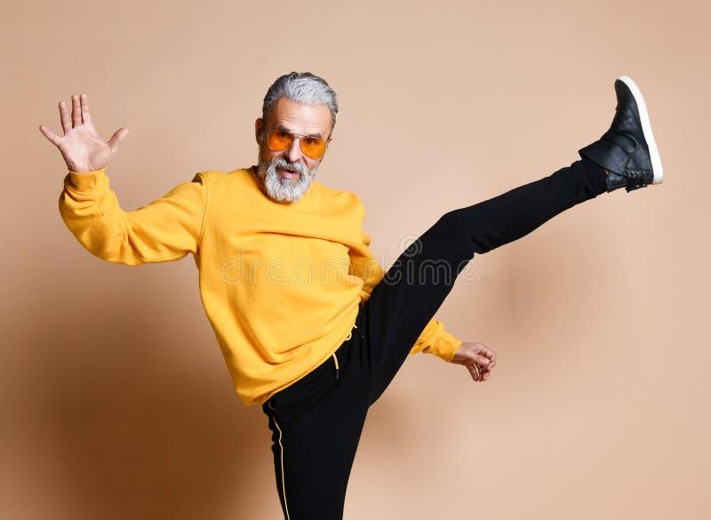 Старый зверский старший человек миллионера делает удар пунша с ногой в людях солнечных очков авиатора стильных модных стоковое изображение rf