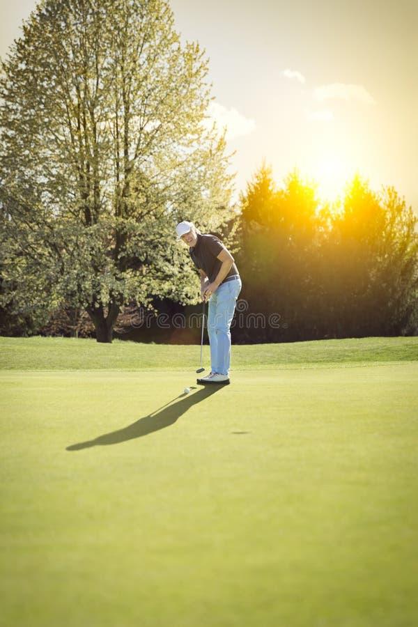 Старый игрок гольфа кладя на зеленый цвет стоковые фотографии rf