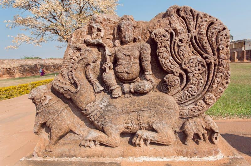 Старый индусский бог сидя на твари льва мифа, руинах каменного резного изображения сброса от виска седьмого века, Karnataka стоковое изображение