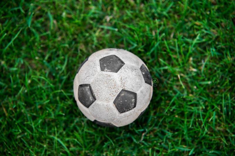 Старый и классический шарик футбольного мяча или футбола на зеленом поле стоковое фото rf