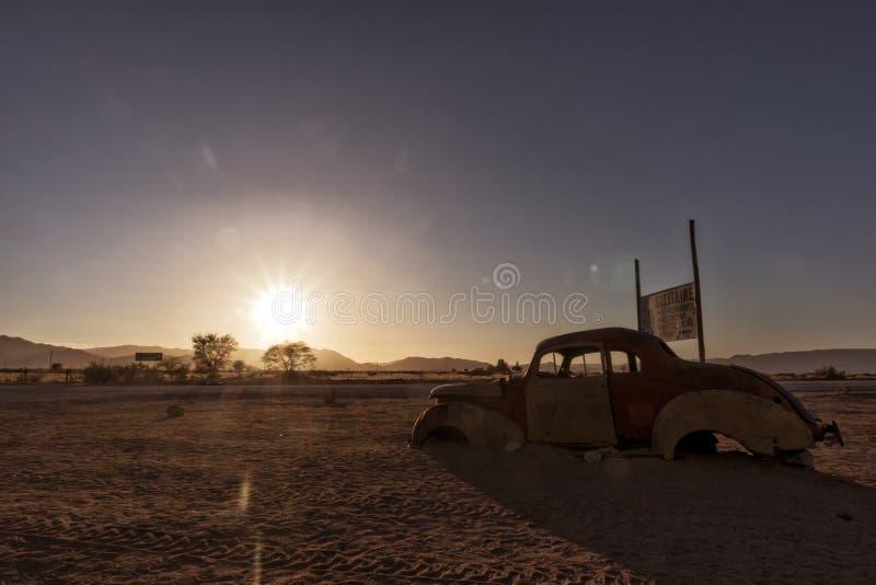 Старый и покинутый автомобиль в пустыне Намибии solitaire С красивым светом восхода солнца стоковое изображение rf