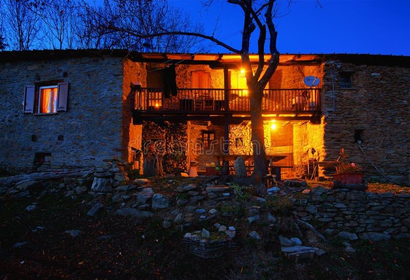 Старый каменный дом горы на наступлении ночи стоковые фотографии rf