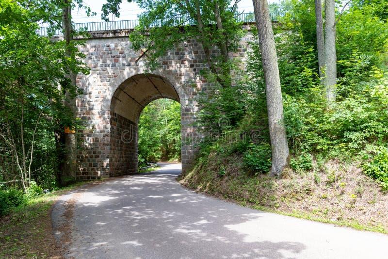 Старый каменный мост над небольшим рекой Железнодорожный переезд через реку в Центральной Европе стоковая фотография