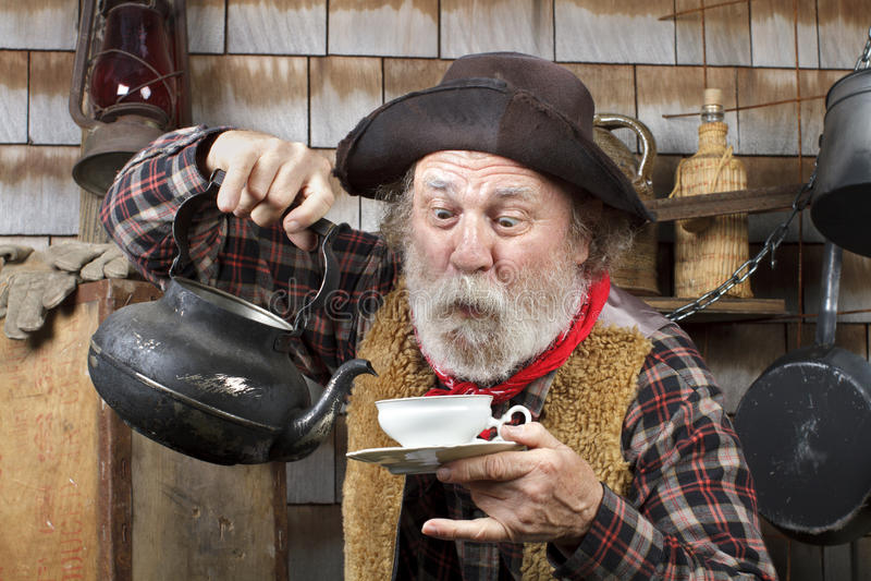 Старый ковбой с чайником и чашкой чая фарфора стоковое изображение