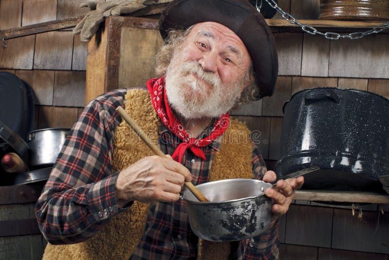 Старый ковбой шевелит кастрюльку в напольной кухне стоковые изображения