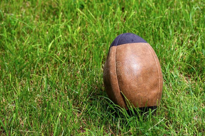 Старый коричневый цвет и черный шарик рэгби на зеленой траве стоковое фото rf