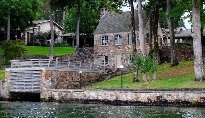Старый коттедж утеса на озере с домом шлюпки стоковые изображения rf