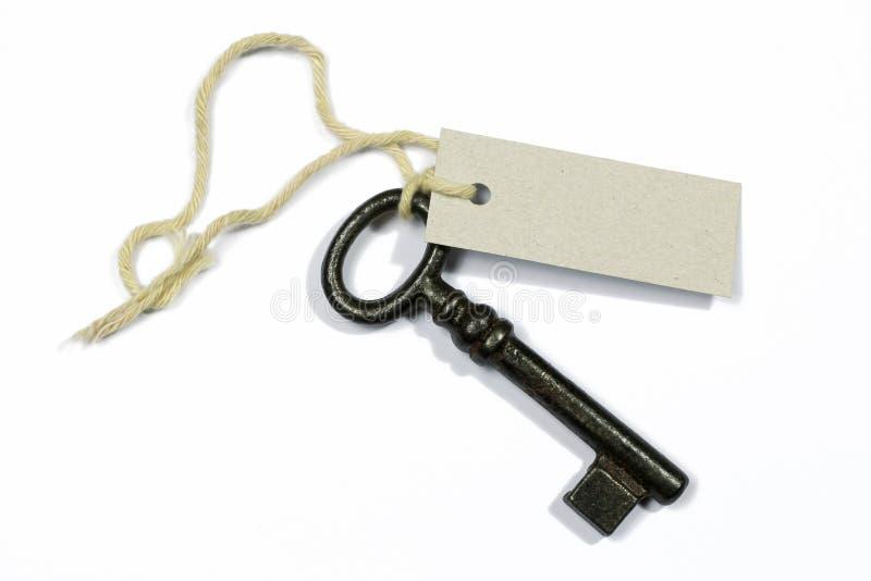 Старый ключ с пустым ярлыком на белизне стоковое изображение