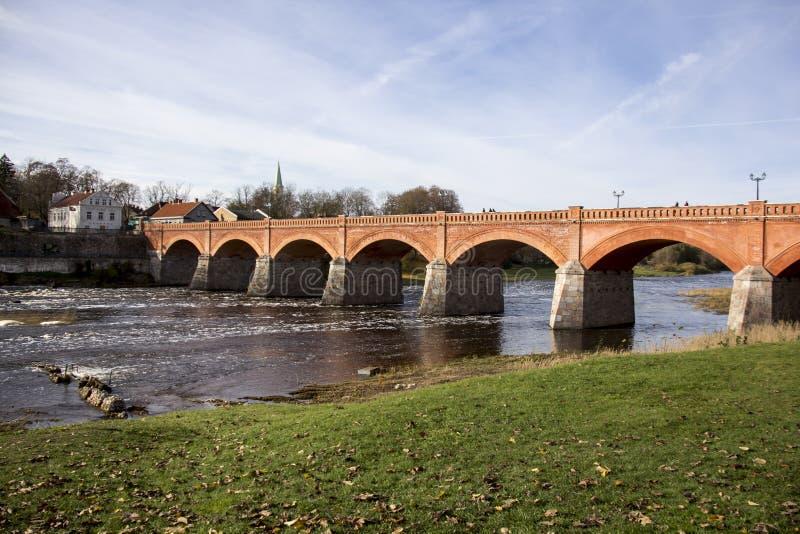 Старый мост кирпича через реку Venta в городе Kuldiga Латвии стоковая фотография