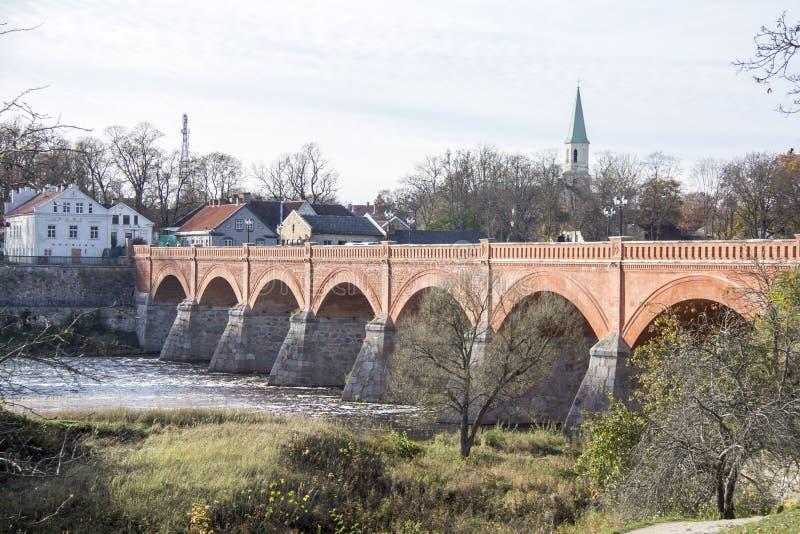 Старый мост кирпича через реку Venta в городе Kuldiga Латвии стоковые изображения rf