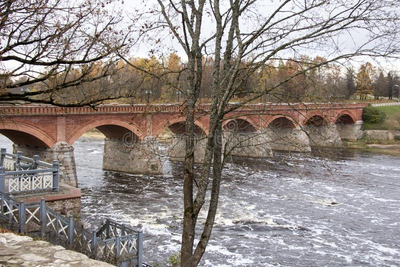 Старый мост кирпича через реку Venta в городе Kuldiga Латвии стоковое изображение rf