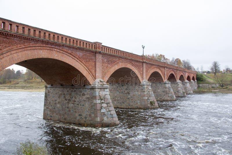 Старый мост кирпича через реку Venta в городе Kuldiga Латвии стоковая фотография rf