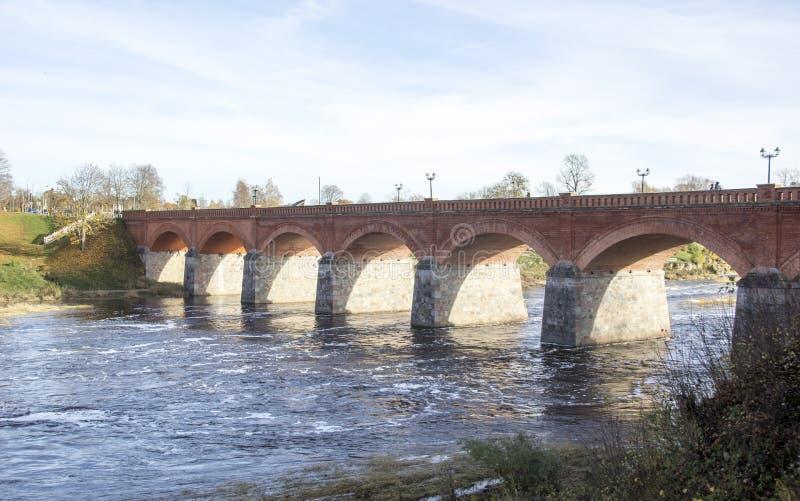 Старый мост кирпича через реку Venta в городе Kuldiga Латвии стоковое фото