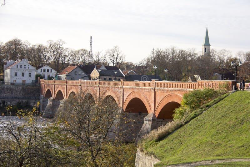 Старый мост кирпича через реку Venta в городе Kuldiga Латвии стоковые фотографии rf
