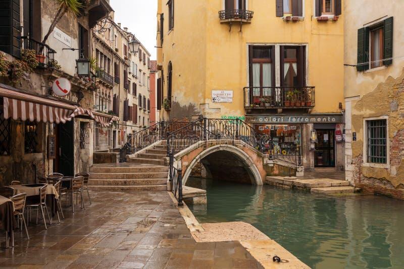 Старый мост над узким венецианским каналом среди старых домов в Венеции, Италии стоковая фотография rf