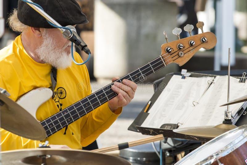 Старый мужской музыкант играя гитару и барабанчики стоковое фото rf