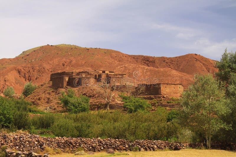 Старый оазис деревни berber со строением домов кирпичей глины перед впечатляющей высокой изрезанной красной стороной горы стоковые изображения